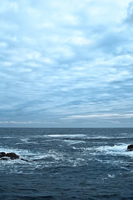 薄曇りの空と岩に砕ける波の画像