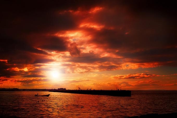 夕焼けの港と沖に向かう舟