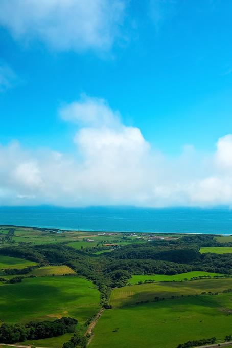 緑の丘の向こうの海辺の写真素材(海の画像)