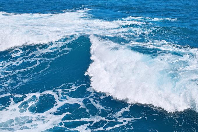 マリンブルーの海に揺れる波