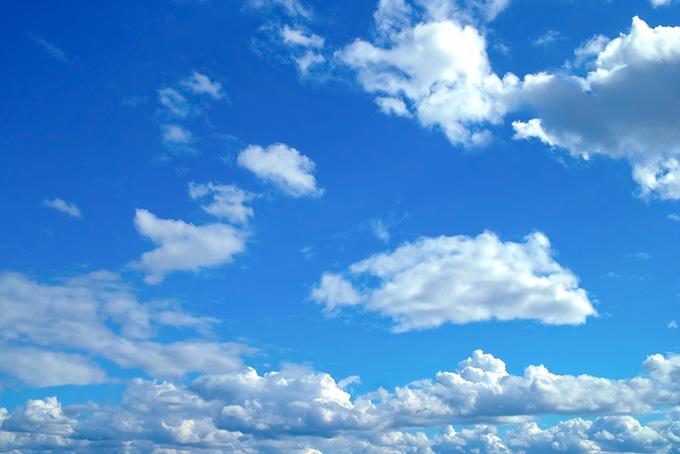 高い空に輝く白い雲の背景
