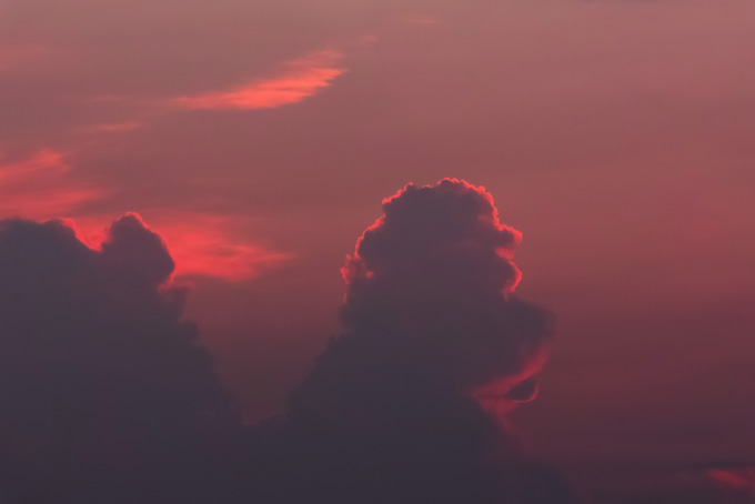 雲のシルエットを照らす夕焼けの光の背景(空 フリーの画像)