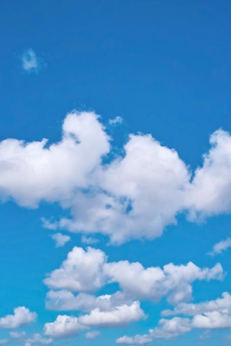 雲がスカイブルーの青空に浮かぶ(空 おしゃれ テクスチャの画像)