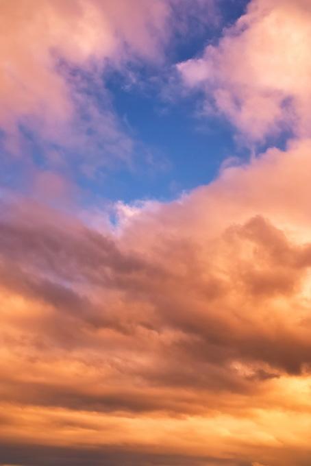 青い空が夕焼けの密雲に覗く(空 おしゃれ テクスチャの画像)