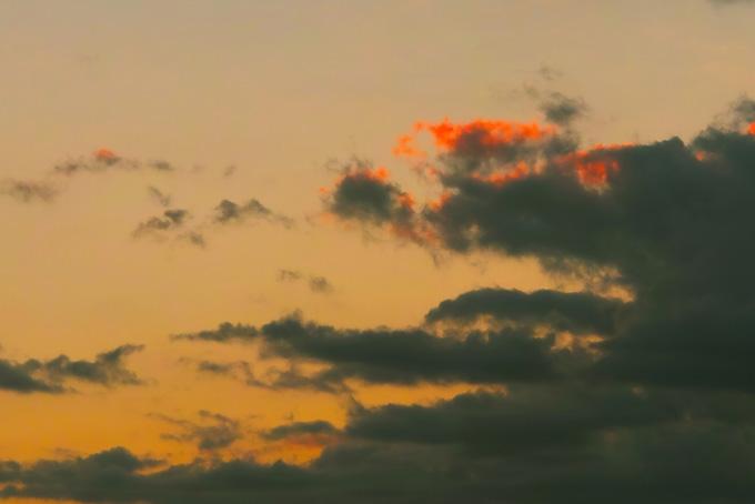 淡い夕焼けに漂う黒雲