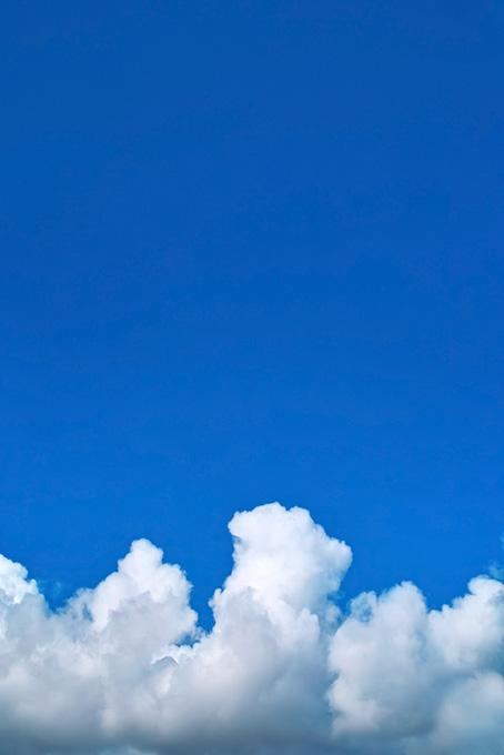 夏の空に登る入道雲の写真