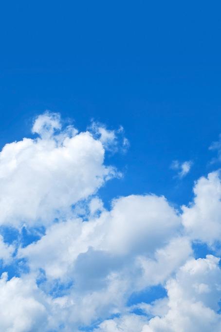 青空の下に群れる綿雲の写真
