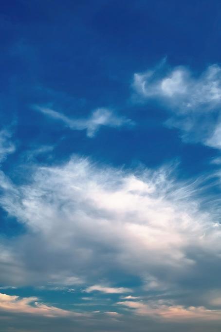 暗い青空と煙の様な大きな雲の写真