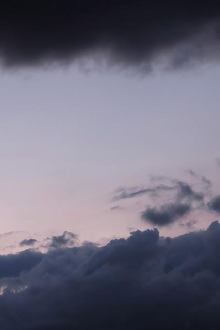 暗雲の間に見える淡い夕焼けの写真