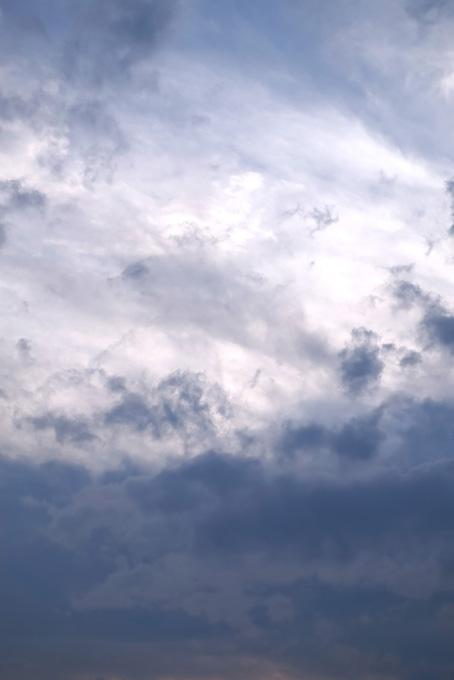 紺鼠色の雲と光に踊る断雲の空の写真