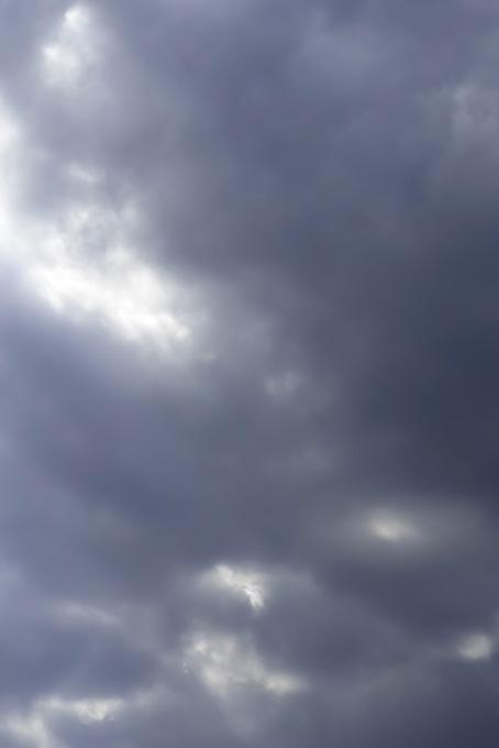 暗雲の空から漏れる光の写真