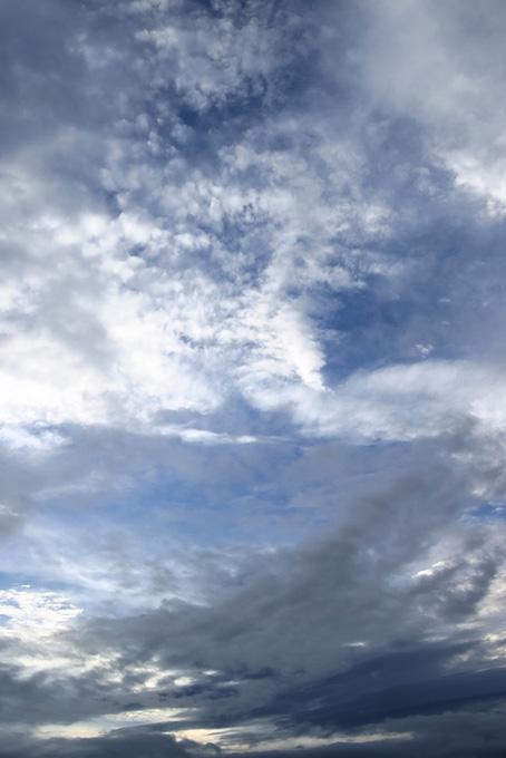 白と黒の薄雲が被さる空の写真