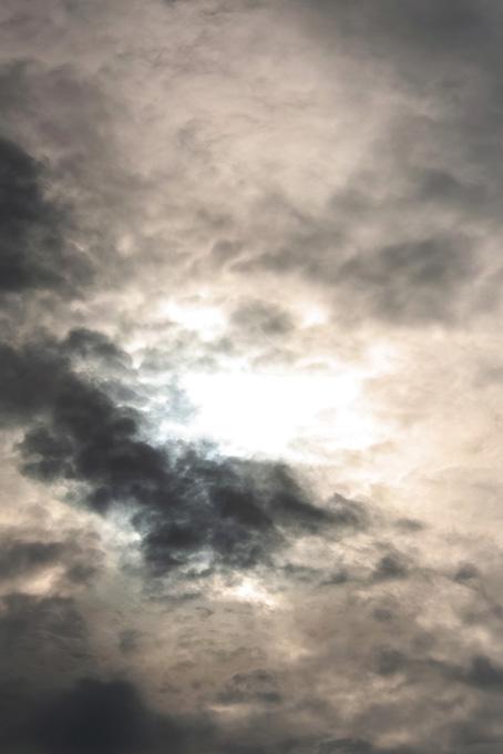 太陽の光が透ける雲が覆う空の写真