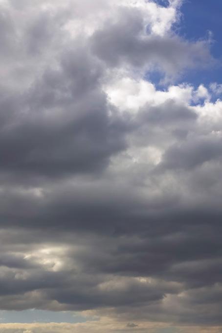 空に遠くまで続く灰色の密雲の写真