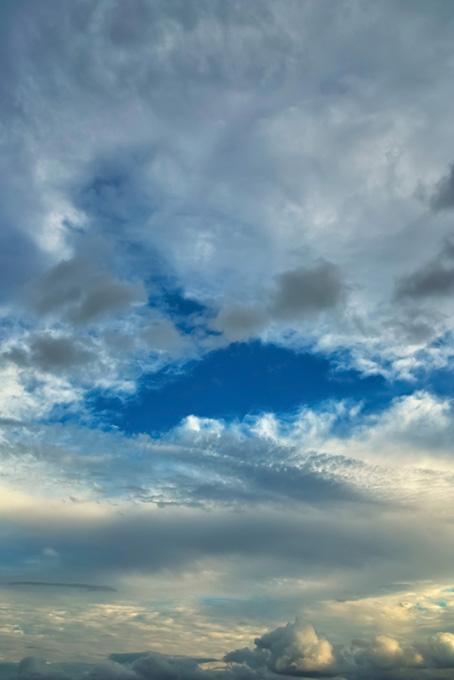 多様な雲の隙間から覗く青空の写真