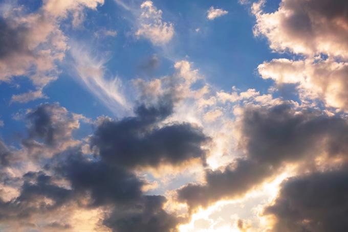 暗い青空に色づき輝く雲