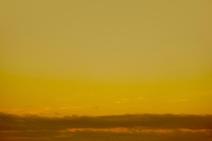 金色の空に黒雲が這う夕焼け