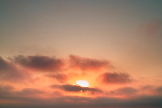 薄暗い朝焼けに朝日が登る