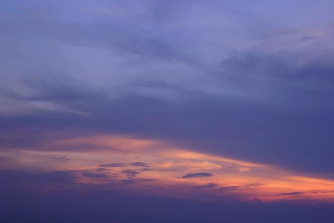 黄丹色の光が伸びる薄暗い夕焼け