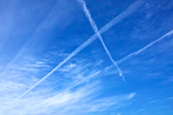 空に交差する飛行機雲(青空 雲のフリー写真)