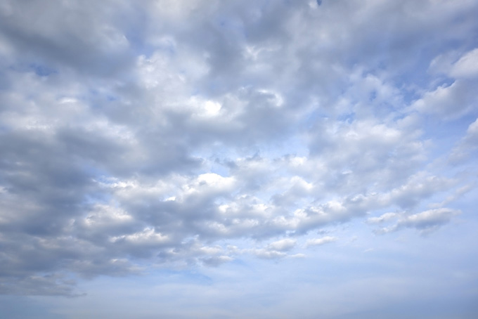 雲が押し寄せる薄く曇った青空の背景