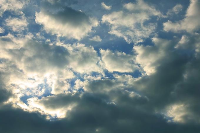 傾く陽に輝く雲と黒い青空