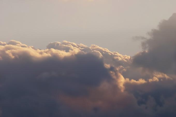 雲の上を照らす淡い夕焼けの光の写真