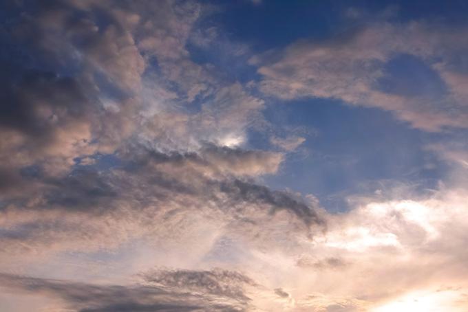 暗い青空を囲む夕焼けの雲の写真