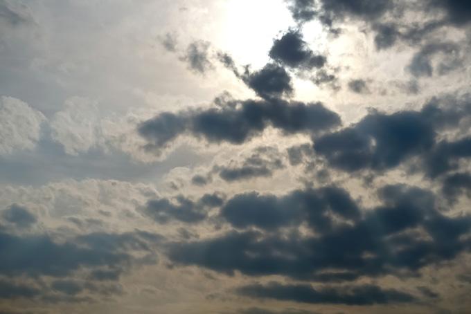 太陽が群れつどう雲を黒く焦がす