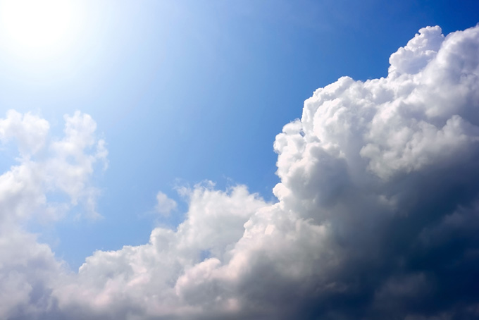 輝く太陽に照らされる雲と青空