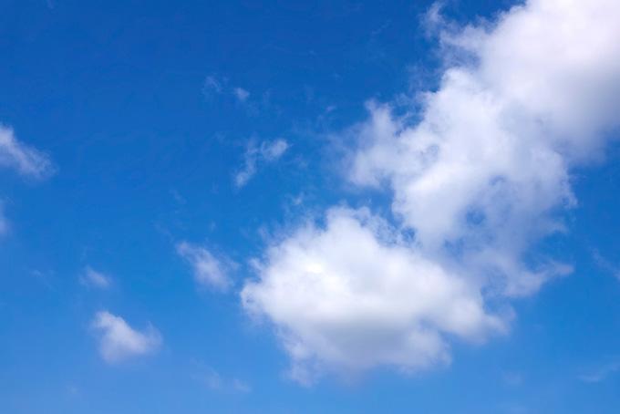 空を登るように浮かぶ白い綿雲の背景