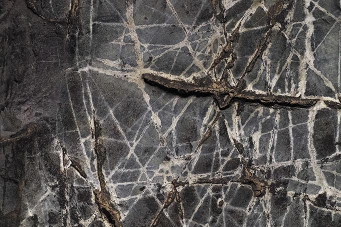 白い線が無数に入った黒い岩(石のフリー画像)