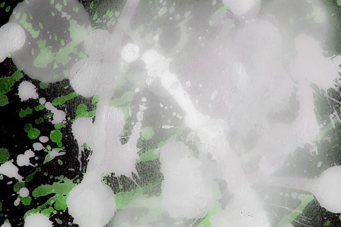 白と緑の絵具を叩きつけた黒背景
