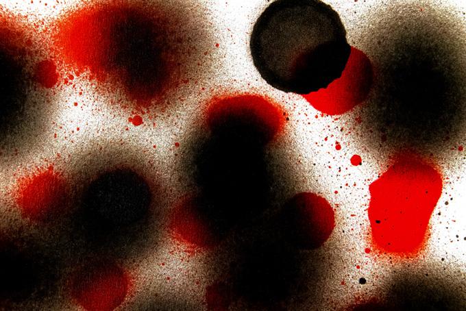 白い紙に黒と赤のスプレー跡